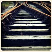 Closeup of train tracks and sleepers. Filtered to look like an aged instant photo.