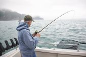 Senior Man Fishing For Salmon In Alaska
