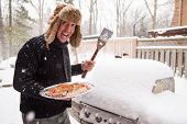 stock photo of sherpa  - a man approaches his grill with a platter of chicken. He is excited about the prospect of BBQ in spite of the big pile of frozen snow