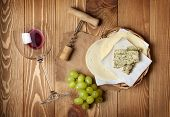 Red wine, cheese and grape on wooden table background