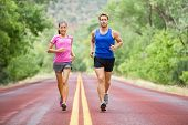 Fitness sport couple running jogging outside on road beautiful nature landscape. Runners training to