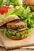 foto of veggie burger  - Vegan burgers with lentils and pistashios stacked on a cutting board - JPG