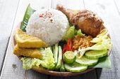 Famous traditional Indonesian food. Delicious nasi ayam penyet with sambal belacan.  Fresh hot with