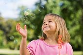 Cute young girl looking at soap bubbles at the park