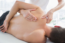 picture of physiotherapist  - Cropped image of physiotherapist massaging man in hospital - JPG