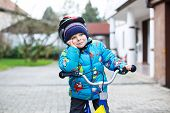 Little Child Of Three Years Riding On Bicycle In Autumn Or Winter, Outdoors