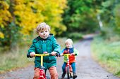 picture of four-wheel drive  - Two active brother boys driving fast on bikes in autumn forest - JPG