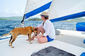 Young woman and her pet dog sailing on a luxury yacht or catamaran boat