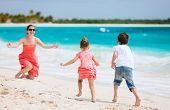Beautiful mother and two kids enjoying beach vacation