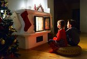 Two little kids sitting by a fireplace at home on Christmas eve