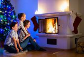 Mother and her two little kids sitting by a fireplace in their family home on Christmas eve