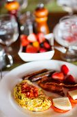 Delicious breakfast with omelet, fresh tropical fruits, berries and cup of hot coffee