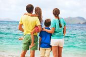 Back view of beautiful family at beach during summer vacation