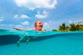 Split underwater photo of adorable little girl with yellow inflatable ring swimming in a pool on sum