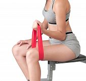 woman exercises with red elastic fitness band