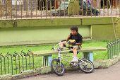 Boy Eating on Bench in Banos, Ecuador