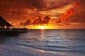 Beach and tropical resort hotel of Maldives on sunset