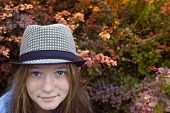 Portrait of a young girl with blue eyes in a hat in the garden.