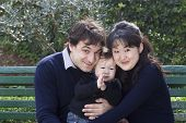 stock photo of nuclear family  - French father and Japanese mother with their baby boy in a park - JPG
