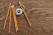 Pencils and school lock on wood surface