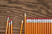 A row of red pencils on wooden surface