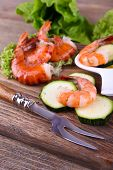Fresh boiled prawns with lettuce and avocado on a wooden rectangular cutting board on wooden backgro