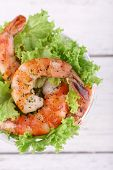 Fresh boiled prawns with lettuce in a goblet on wooden background