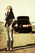 Fashion woman with broken car calling on the cell phone