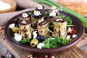 Fried aubergine with cottage cheese in a round plate on wooden cutting board on wooden background
