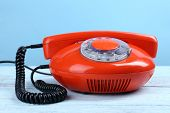 Retro red telephone on color background, close up