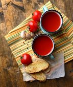 Homemade tomato juice in color mugs, toasts and fresh tomatoes on wooden background