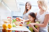 Girls making salad with their mother