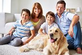 Happy family of four with a dog