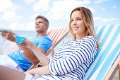 Couple resting in deck chair with martini