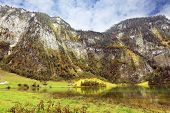 Cloudy day in the Bavarian lake Koenigssee. Clouds and mountains reflected in the water
