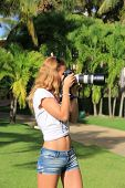 Girl With The Camera On A Sunny Day Among Palm Trees