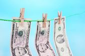 Dollar bills hanging on rope attached with clothes pins. Money-laundering concept. On bright backgro