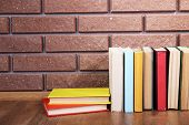 Books on wooden table on brick wall background