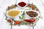 Spices in glass round bowls with herbs and chilly pepper on wooden background