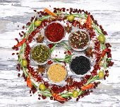 Spices with herbs and dried chilly pepper on wooden background