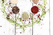 Spices in glass round bowls with herbs on wooden background