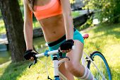 A portrait of a beautiful young woman with her bike outdoor