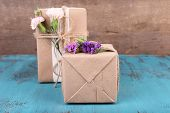 Beautiful gifts with flowers, on old wooden background