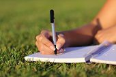 stock photo of writing  - Close up of a woman hand writing on a notebook outdoor lying on the grass in a park - JPG