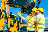 stock photo of engineering construction  - Asian worker at construction machinery of construction site or mining company - JPG