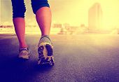 a woman with an athletic pair of legs going for a jog or run during sunrise or sunset - healthy lif