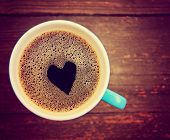 a cup of coffee with a heart shape toned with a retro vintage instagram filter