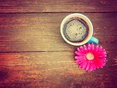 a cup of coffee and a flower on a wooden texture background toned with a retro vintage instagram fil