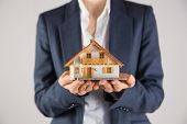 Businesswoman holding miniature model house on grey background