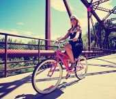 a pretty girl riding a bicycle across a bridge toned with a retro vintage instagram like filter